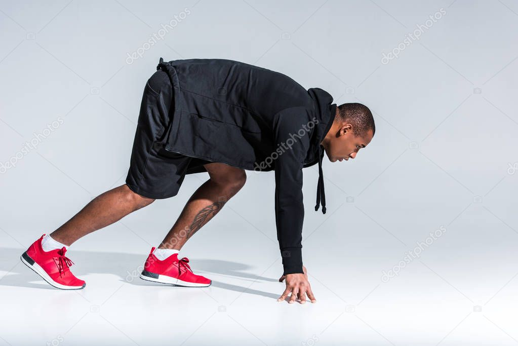 side view of young african american sportsman in hoodie ready to run on grey