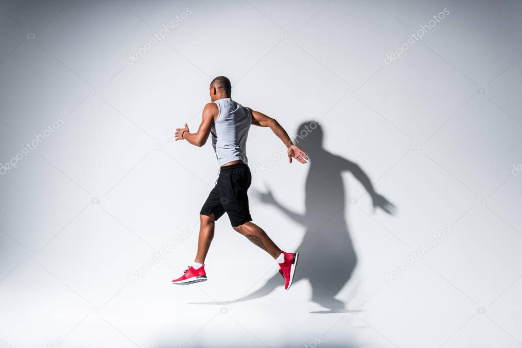 full length view of young african american sportsman running on grey