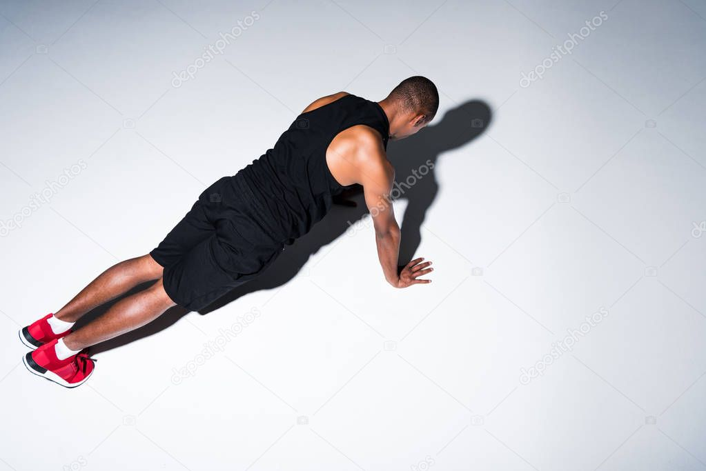 high angle view of athletic african american sportsman doing push ups isolated on grey