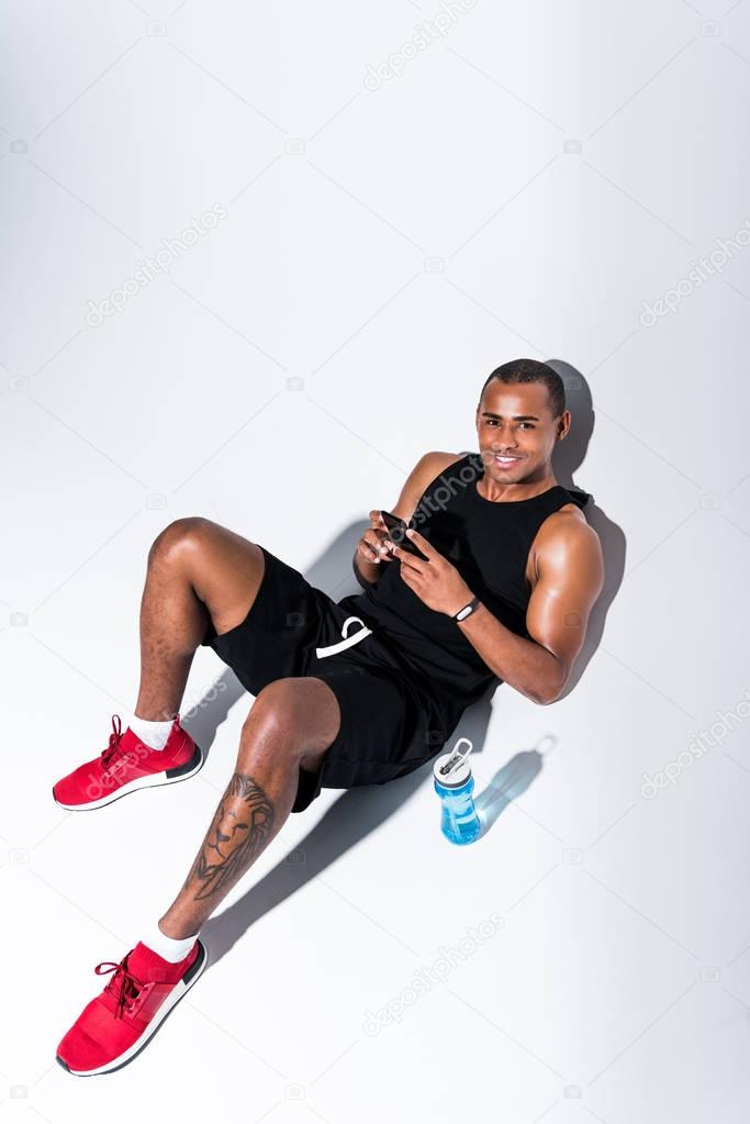 high angle view of handsome african american sportsman using smartphone and smiling at camera on grey