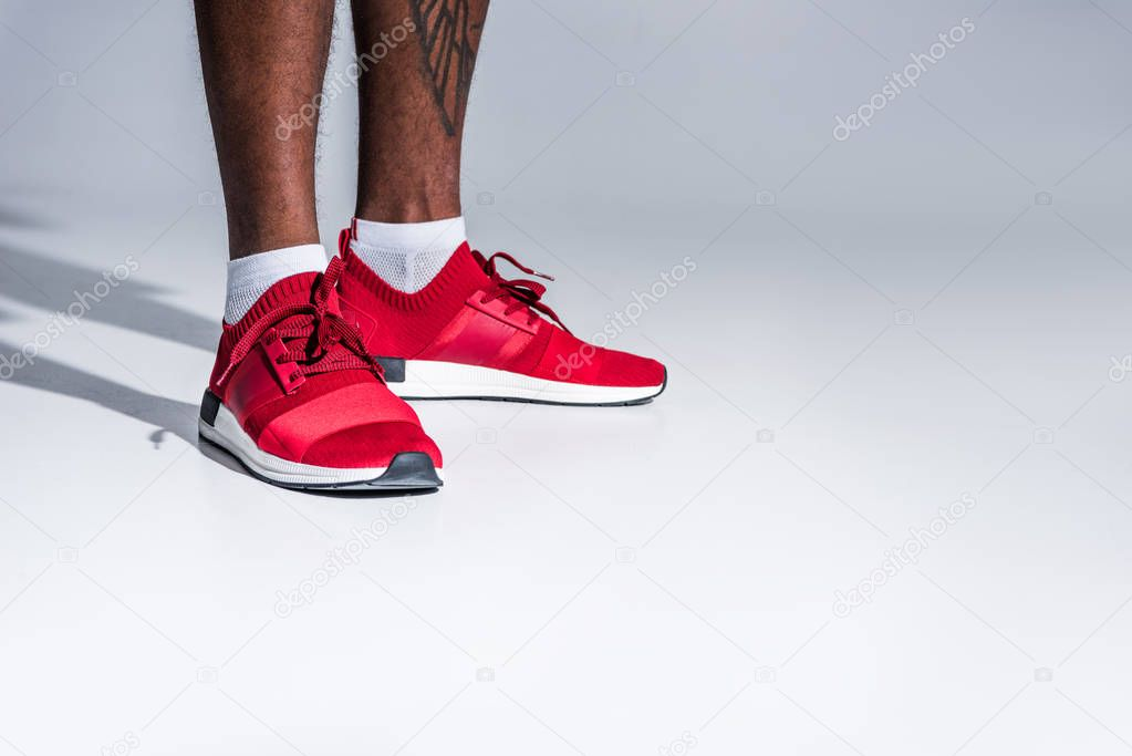 close-up partial view of african american man in sports shoes standing isolated on grey