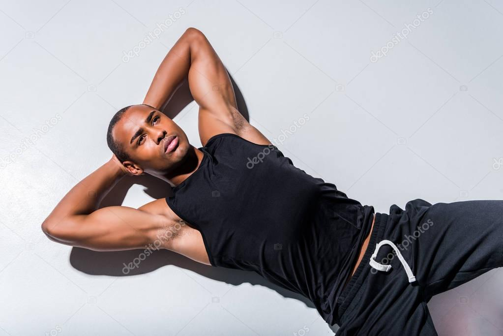 handsome young african american sportsman lying with hands behind head and looking away on grey