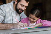 Fotografie happy father with little daughter sitting at table and drawing in scrapbook at home