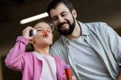 boldog apa és lánya fúj buborékok otthon