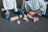 Fotografie cropped image of father with daughter making words by cubes with letters at home