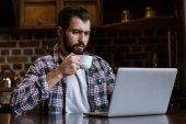 szép ember ül az asztal, laptop kávéscsésze