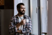 Happy pohledný muž s šálek kávy při pohledu na okna