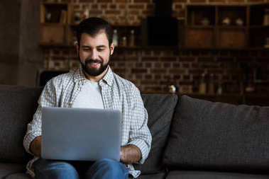 handsome man sitting on couch and using laptop