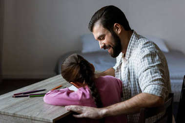 side view of father with little daughter sitting at table and drawing in scrapbook at home