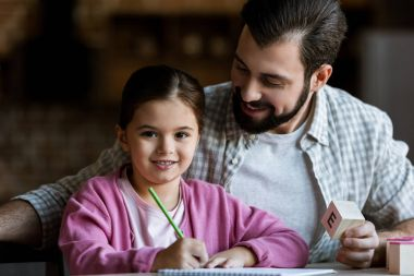 father with daughter sitting at table with cube letters and drawing at home
