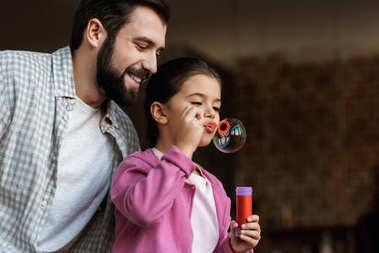 happy father with daughter blowing bubbles at home