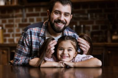 happy father with daughter sitting at table and looking at camera at home