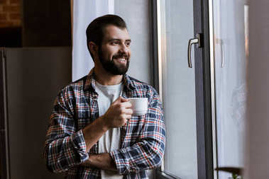 Happy handsome man with coffee cup looking at window stock vector