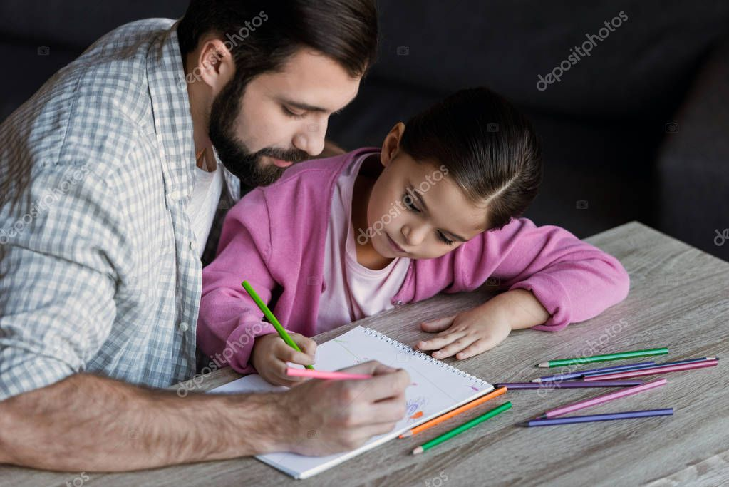 father with little daughter sitting at table and drawing in scrapbook at home