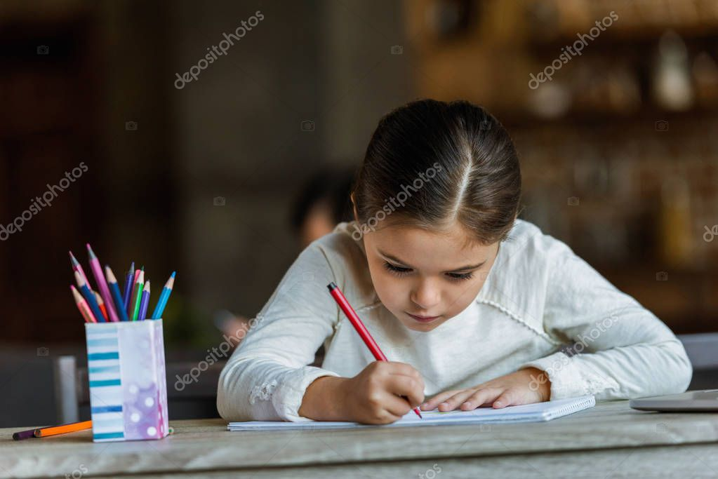 little child sitting at table and drawing in scrapbook at home