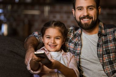 happy father with daughter sitting in couch, hugging and watching TV at home