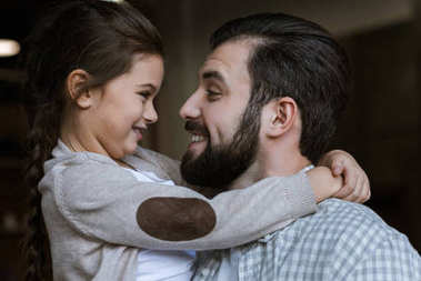cheerful father and daughter hugging and looking at each other at home