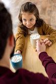 Fényképek felülnézete boldog lánya és apa megváltozó a csésze cacao, fehérmályva