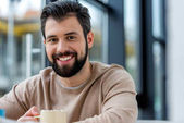 smiling handsome man holding cup of coffee with marshmallow and looking at camera