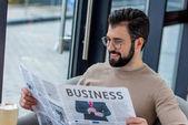 usmíval se podnikatel v brýlích, čtení novin v kavárně