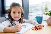 Rozkošné dítě drží barevné pastelky a při pohledu na fotoaparát