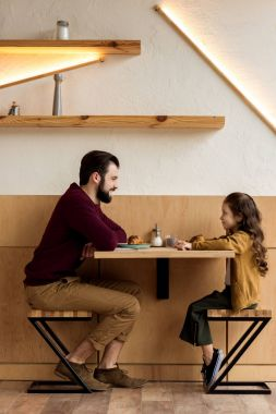 father and daughter sitting in cafe with croissants