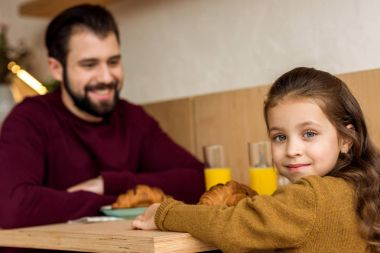 adorable daughter sitting with father in cafe and looking at camera