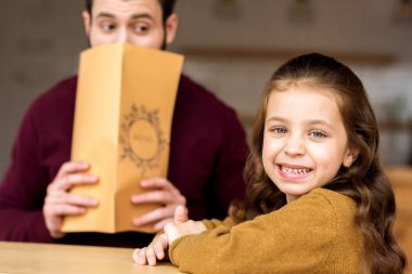 smiling daughter looking at camera and father looking out from menu in restaurant