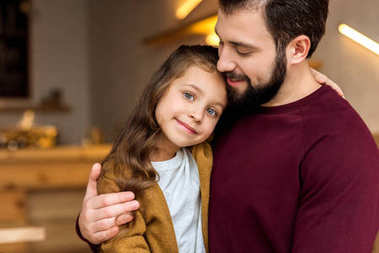 father and adorable daughter hugging in cafe