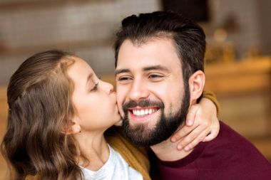 portrait of daughter kissing smiling father in cafe