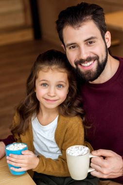 smiling father and daughter holding cups of cacao with marshmallow and looking at camera