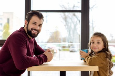 father and daughter holding cups and looking at camera