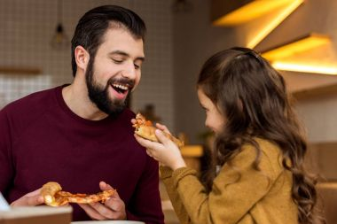 daughter giving father to bite a piece of pizza