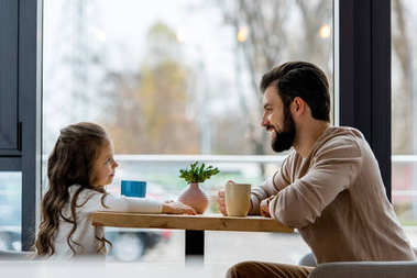 happy father and daughter sitting in cafe and looking at each other