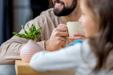cropped image of smiling father holding cup of coffee in hands