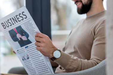 cropped image of smiling businessman sitting in cafe and reading newspaper