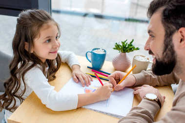 smiling daughter and father drawing together and looking at each other