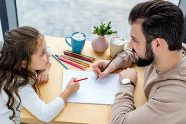 father and daughter drawing and looking at each other