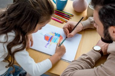 father and daughter sitting at table and drawing in album