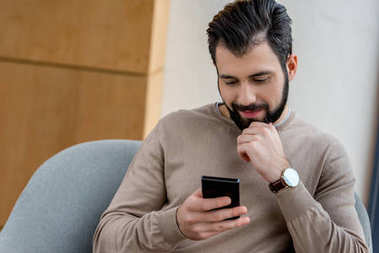 handsome man sitting in armchair and looking at smartphone