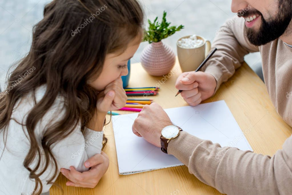 cropped image of father holding pencil and showing watch to daughter