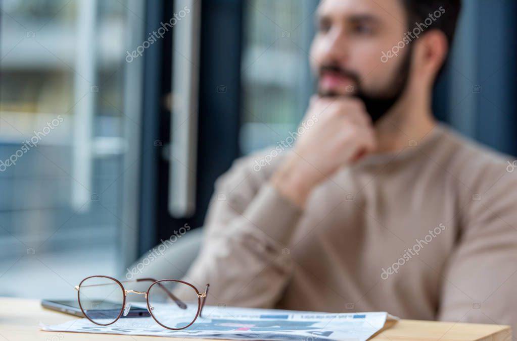 thoughtful man sitting in cafe with glasses on foreground