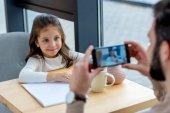 Bild des Vaters Aufnahme Fotos von lächelnden Tochter im Café beschnitten