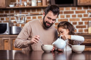 daughter pouring milk to father plate in kitchen