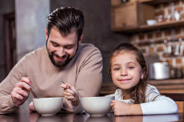 happy daughter and father having breakfast