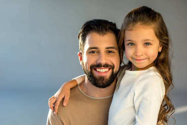 portrait of happy father and daughter looking at camera