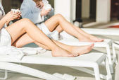 Fotografie cropped shot of women with beautiful legs drinking coffee at spa center while sitting on sunbeds