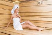 atraktivní mladá žena uvolňující na lavici v sauně