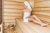 schöne junge Frau entspannt sich auf Bank in der Sauna