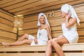 krásné mladé ženy sedí na lavičce sauna a mluví